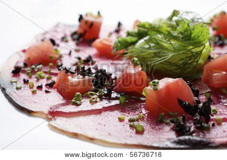 voorhoede van carpaccio van tonijn met in blokjes gesneden tomaten
