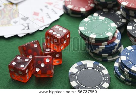 dices, cards and casino chips on a green baize