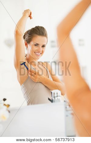 Happy Young Woman Using Shaving Armpit In Bathroom
