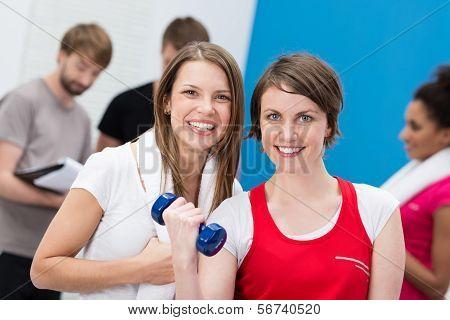Young Woman Lifting Weights Aided By A Friend