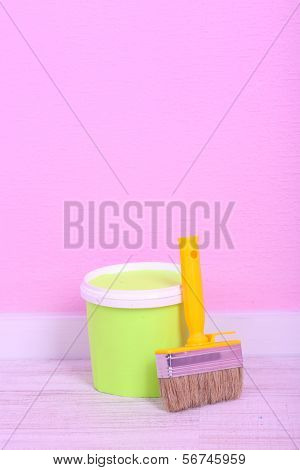 Paint and paintbrush on floor in room on wall background