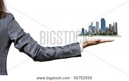 Back view of businesswoman holding in palm tablet pc with city image