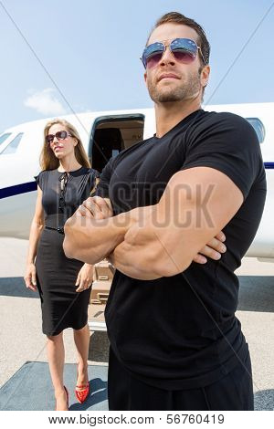 Bodyguard with arms crossed standing against woman and private jet