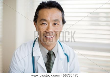 Portrait of Asian male cancer specialist with stethoscope around neck smiling in clinic