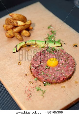 Beef tartare with french fries and avocado on table