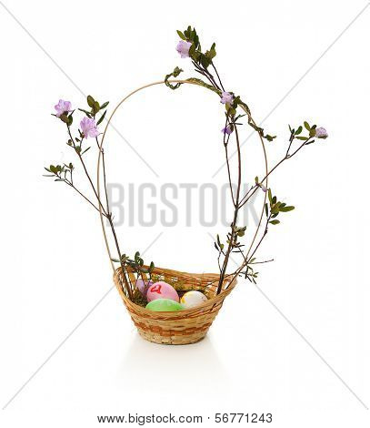 easter basket with blooming twigs of ledum isolated on white