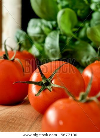 Ripe Tomatoes, Basil And A Bottle Of Wine On A Wooden Table