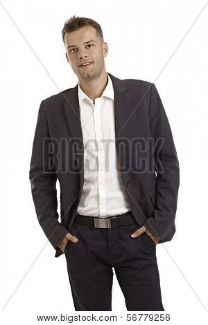 Confident young businessman standing hands in pockets.