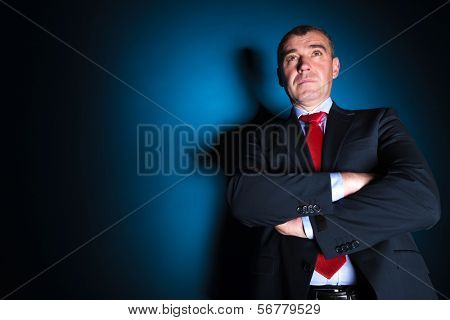 serious old business man with arms folded looking away from the camera