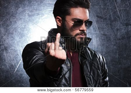 fashion man in leather jacket and sunglasses flipping you off