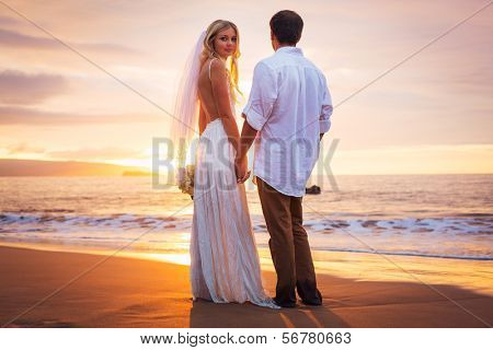 Married couple, bride and groom at sunset on beautiful tropical beach in Hawaii