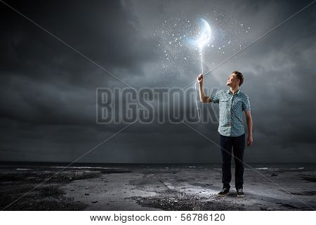 Young man holding moon balloon against dark background