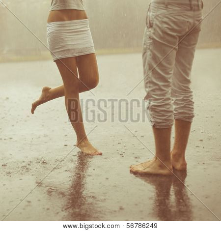 A loving young couple hugging and kissing under a rain. Two lovers, man and woman barefoot in the shower. Summer in love
