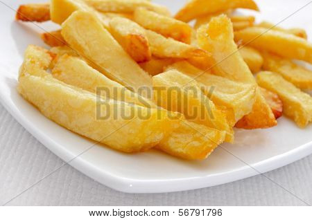 closeup of a plate with appetizing french fries on a set table