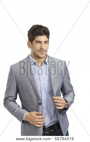 Portrait of young businessman unbuttoning jacket, looking away.