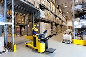 stock photo of hand truck  - Huge metal stillage and yellow hand pallet truck in warehouse - JPG