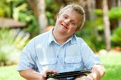 Boy Wih Down Syndrome Playing On Tablet.