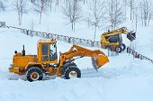 stock photo of wheel loader  - Snowplows on clearing snow drifts - JPG