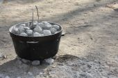 image of dutch oven  - Cast Iron Dutch Oven Covered in Charcoal - JPG
