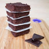 foto of chocolate fudge  - Fresh Homemade Vegan Chocolate Brownies stacked separated with parchment paper with two pieces of da