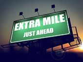 Постер, плакат: Extra Mile Just Ahead on Green Billboard