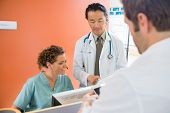 picture of reception-area  - Doctor and nurse using digital tablet while patient standing at reception in hospital - JPG