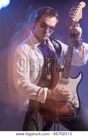 Portrait Of Male Guitarist Playing With Expression. Shot With Strobes And Halogen Light On Slow Shut