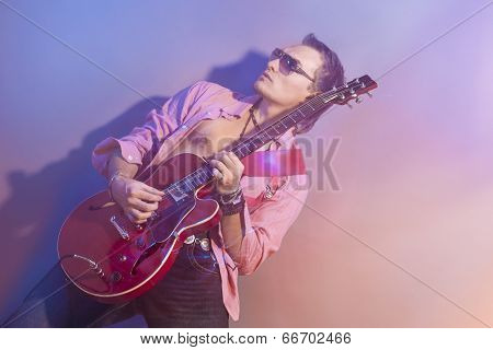 Male Guitarist Playing The Electric Guitar. Shot With Strobes And Halogen Light To Create Mood And A