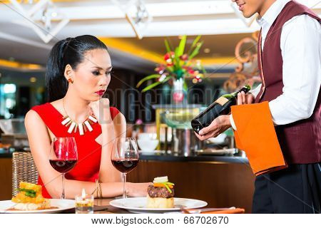 Waiter showing bottleof wine in restaurant
