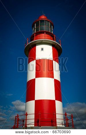 Towering, Tall Lighthouse Against Deep Blue Sky