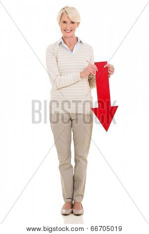 beautiful senior woman holding red arrow pointing down on white background