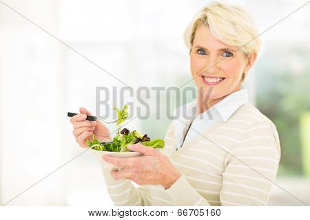 cheerful mature woman having green salad