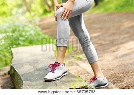 A picture of a jogger having problems with knee in the forest