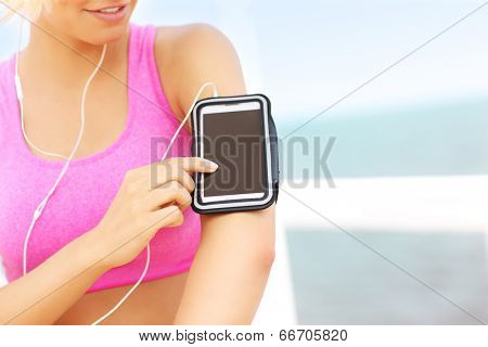 Close up of fit woman touching phone placed in armband