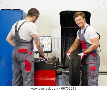 Two mechanics balancing wheel in a car workshop