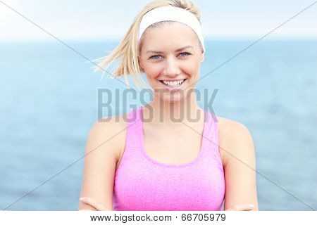 Young Woman in pink sports bra over sea