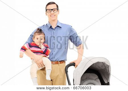 Young father holding his baby daughter and pushing a baby stroller isolated on white background