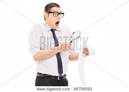Man with magnifier looking at a bill in disbelief isolated on white background
