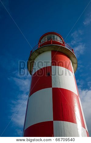 Looking Up At Towering Red And White Lighthouse