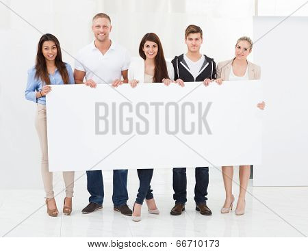 Confident Businesspeople Holding Blank Billboard