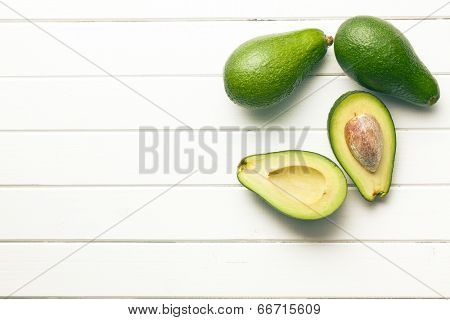 top view of halved avocados on wooden background
