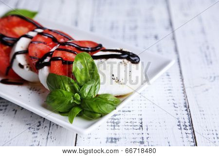 Caprese salad with mozarella cheese, tomatoes and basil on plate, on wooden table background