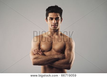 Bare-chested Muscular Man Standing On Grey Background