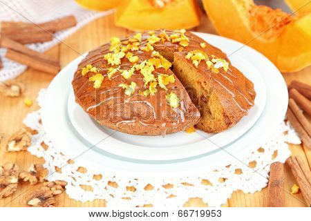 Delicious pumpkin pie on plate on wooden table close-up