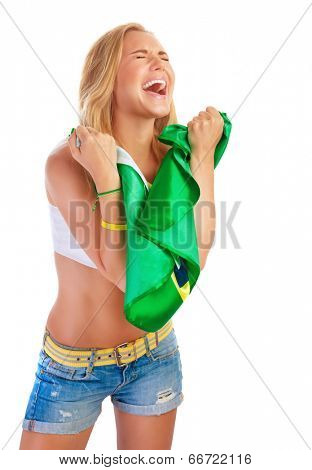 Portrait of beautiful young girl is glad to the goal that Brazil hammered, holding in hands Brazilian flag and screaming of pleasure with closed eyes, isolated on white background