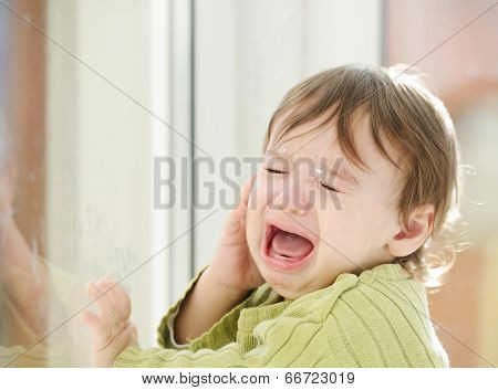 Sick baby standing and waiting on window glass