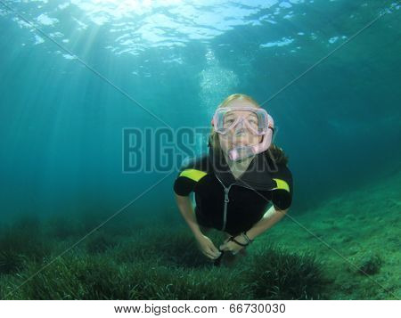 Young woman snorkeler dives in the ocean