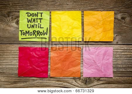 do not wait until tomorrow - motivational reminder - handwriting on sticky note against grained wood