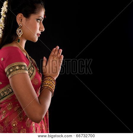 Beautiful Indian girl in greeting pose, traditional sari prayer isolated on black background with copy space on side.