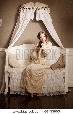 Beautiful young girl in a vintage dress. Gentle pretty woman the classic interior.
